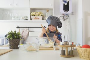 Happy little girl chef mixing the dough with big wooden spoon in glass bowl