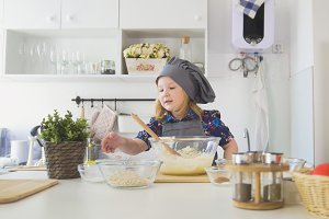 Cute little girl chef pointed hand on bowls with ingredients for cooking