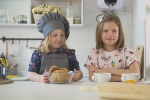 Two little sisters smiling with homemade cookies and cups of tea at cooking studio