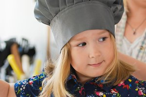 Cute little girl chef in hat smiling at cooking studio