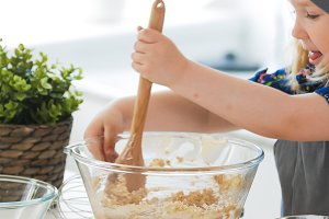 Cute little girl mixing the dough for cookies with wooden spoon in glass bowl