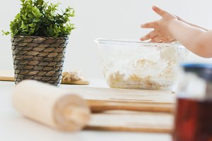 Hands of little girl mixing the dough for cookies in glass bowl