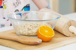 Oatmeal in glass bowl and orange with wooden rolling pin for cooking biscuits