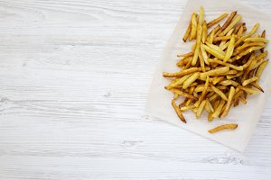 French fries on white wooden board