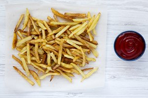 Tasty fries with ketchup on white