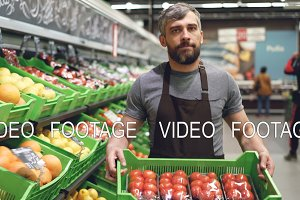 Dolly shot of young salesman in apron carrying box of tomatoes in supermarket in fruit and vegetables department. Salesperson, food store and prosefession concept.