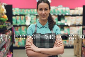 Portrait of attractive young saleswoman in apron standing in supermarket with her hands crossed, looking at camera and smiling. Trade business and people concept.