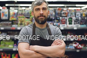 Portrait of handsome bearded guy experienced salesman in apron standing in toy department in supermarket, looking at camera and smiling. Shop and people concept.