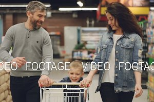 Slow motion of cheerful people happy family running in food store with shopping trolley and laughing, boy is pushing cart and his parents are helping him.