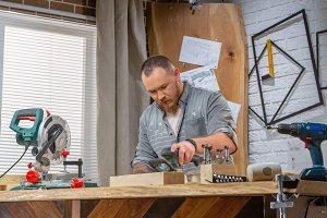 Man sawing wood with a circular saw on a workbench