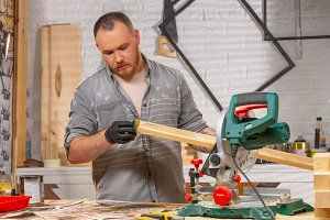 the joiner covers varnish the wooden part in workshop