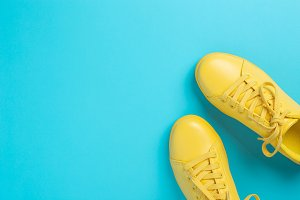Pair of yellow shoes on blue background.