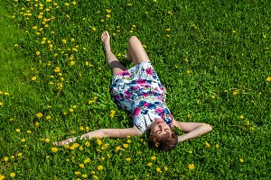 A woman in a cotton dress lies on the green grass with dandelions