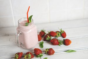 Healthy strawberry smoothie with scattered ripe berries on the table