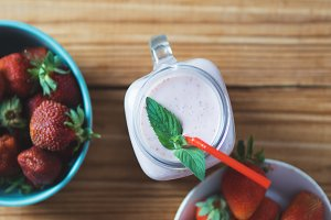 Delicious strawberry smoothie on a wooden background with grapes