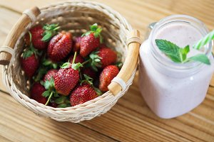 Strawberry yogurt or smoothie on a wooden background with ripe berries