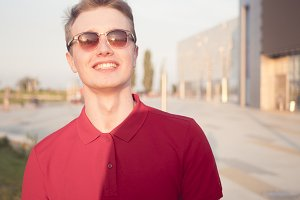 happy young man smiling in sunglasses standing outdoor