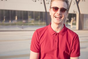 portrait of young laughing hipster in sunglasses with copy space text