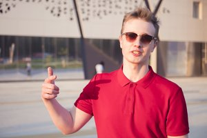 young male hipster in red polo outside talking with gesticulates