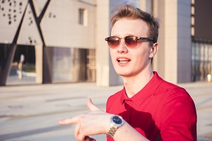 portrait of young hipster talking outside and gesticulates with hands