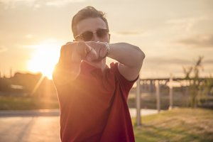 young hipster outside in the street pointing in the camera during sunset