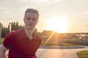 portrait of beautiful trendy man wearing red top and sunglasses outdoor during sunset