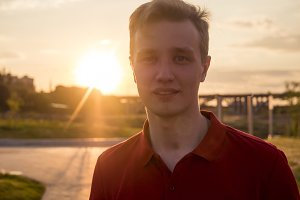beautiful handsome man portrait with copy space walking outdoors in the city during sunset