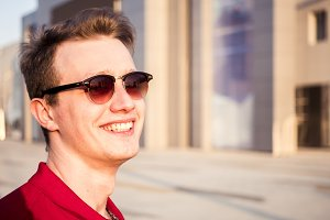 laughing handsome young man portrait wearing red shirt and sunglasses