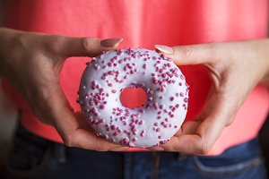 Female hands hold a delicious donut.
