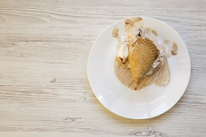 Ice cream cone on a white plate.