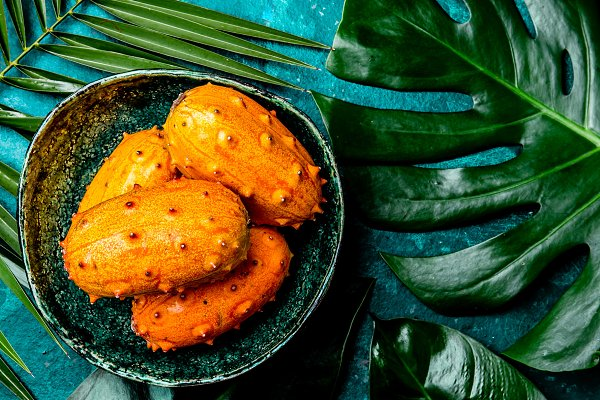 Nature Stock Photos: LARISA BLINOVA - Tropical fruin KIWANO passion fruit in green bowl on turquoise background with tropical palm tree leaves. Top view. Tropical concept