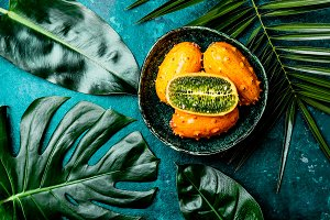 Tropical fruin KIWANO passion fruit in green bowl on turquoise background with tropical palm tree leaves. Top view. Tropical concept