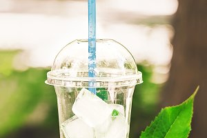 a glass of juice with ice. leaves of mint, straws for drinks. drink in the open air