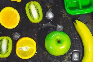 kiwi and orange sliced. ice in cubes. banana. green apple