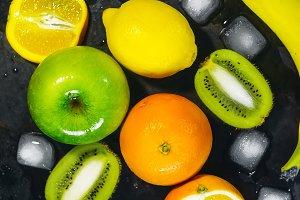 fruits and ice cubes. citrus apple, kiwi and banana