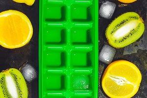 Form for ice. green color. fruit. kiwi, orange, lemon