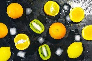 citrus, kiwi, apple. ice on a black background
