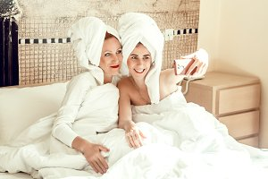 mom and daughter. love and care. girls in the towels at home make a photo on the phone for memory. house.