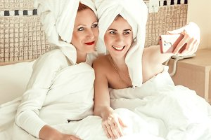 mom and daughter spend time together. under a blanket and in towels make a photo in bed. love. a family.