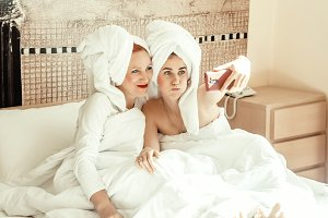 warm relations between mother and daughter. spend time together. body care . towel on the head. are pointed at the camera. picture for memory