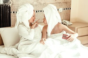 Mom and daughter are playing. time together. body care. towel on the head. Mom wants to touch the nose of her daughter.