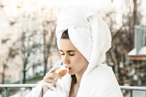 girl. a glass of champagne. girl on the balcony in a towel after a bath. outdoor recreation. gulp of drink