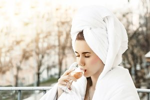 girl in towel with wet hair. in the hands of a glass. sip for relaxation. good weather on the loggia