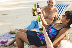 Mature friends having beers at beach