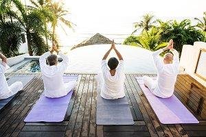 Senior friends doing yoga near pool