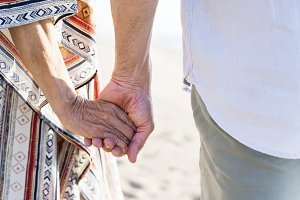 Mature couple holding hands at beach