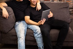 Gay couple watching and looking at phone tablet together. Portrait of happy gay men - Homosexual love concept