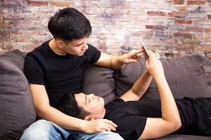 Asian gay couple watching and looking at phone tablet together. Portrait of happy gay men - Homosexual love concept