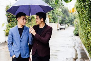 Gay couple holding umbrella and hands together. Asian homosexual men walking in the rain