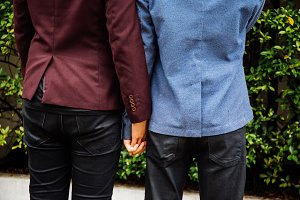 Gay couple holding hands together. Back of homosexual men walking in the park
